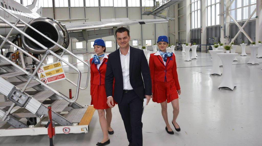 пилотът Марио Бакалов и две стюардеси от екипажа в самолетен хангар